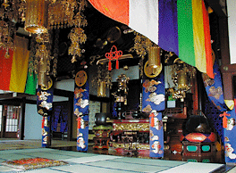 A statue of the Sacred Kannon behind the splendidly ornamented main altar or Shumidan.