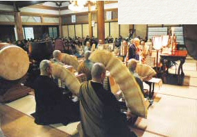 New Year prayers. Priests manipulate accordion-pleated sutras in flowing arcs.